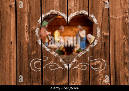 Looking through a carved heart in a wooden wall to nativity scene in stable of Bethlehem - Stock Photo