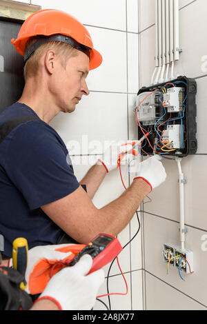Electricians are checking the voltage at the terminals of the electrical meter. They are using a multimeter. - Stock Photo