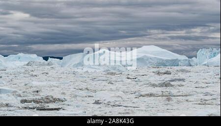 Iceberg aerial drone image - giant icebergs in Disko Bay on greenland floating in Ilulissat icefjord from melting glacier Sermeq Kujalleq Glacier, Jakobhavns Glacier. Global warming, climate change