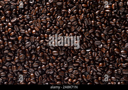 Dark roasted coffee beans. Rustic background with space for text - Stock Photo