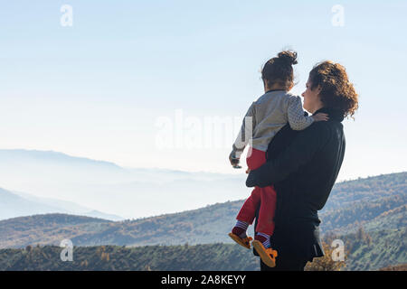 Young mother with little daughter looking at mountains on vacation, family travel together on top of high mountain outdoors, looking at beautiful land