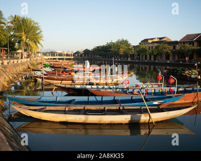 Sunlit row of colorful wooden fishing boats, some with lanterns, moored in the Thu Bon River in Vietnam. - Stock Photo