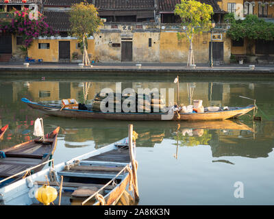 Wooden fishing boats with eyes painted on hulls docked in the Thu Bon River in Hoi An, Vietnam. Gold stucco buildings live the river. - Stock Photo