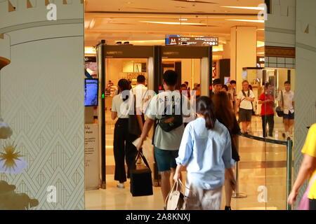 Bangkok, Thailand - November 8 2019 : Blurred motion of group of people walking through metal detector at entrance of Siam Paragon shopping mall - Stock Photo