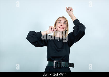 Young woman in dark clothes rising hands, clenching fists like winner