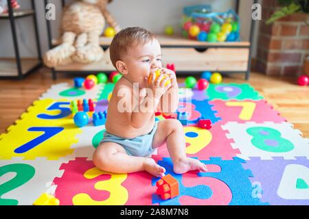 Beautiful toddler sitting on the puzzle carpet toy playing with colorful balls at kindergarten - Stock Photo