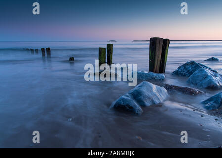 Outgoing waves and incoming tide. meet round the groynes and rocks.  The blue hour on Youghal strand. - Stock Photo