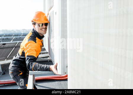 Professional workman in protective clothing installing outdoor unit of the air conditioner or heat pump on the rooftop - Stock Photo