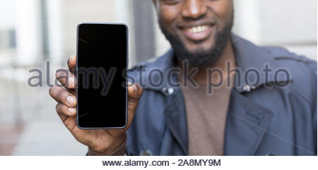 Close up potrait of african man in autumn jacket holding a smart phone with screen for copy space. - Stock Photo