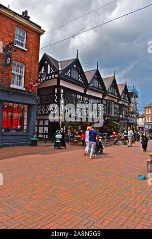 A busy scene in the historic Nantwich town square with people passing quaint half-timbered black & white buildings. Others eating and drinking outside - Stock Photo
