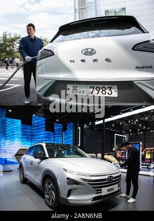 (191110) -- SHANGHAI, Nov. 10, 2019 (Xinhua) -- Combo?photo?shows an employee charging a Hyundai Nexo Hydrogen fuel cell car in Yongin,?South?Korea, Oct. 22, 2019 (top, photo by Wang Jingqiang), and an employee cleaning a Hyundai Nexo Hydrogen fuel cell car during the second China International Import Expo (CIIE), Nov. 5, 2019 (bottom, photo by Liu Yun) Wines from Argentina, mineral water for Malaysia, health care products from Australia, diesel engine from France, Hydrogen fuel cell vehicle from South Korea . Exhibitors from all around the world showcased their high quality goods at the sec - Stock Photo
