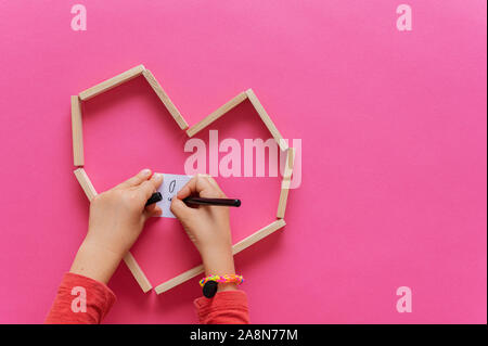 Top view of child's hands drawing on white post it paper placed in a heart shape made of wooden pegs. Over pink background with copy space. - Stock Photo
