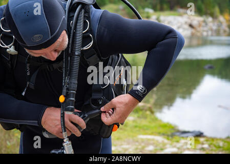 Paayanne lake, Finland - September 2019. Diver checks equipment near the lake. Male diver in wetsuit checking equipments before immerse - Stock Photo