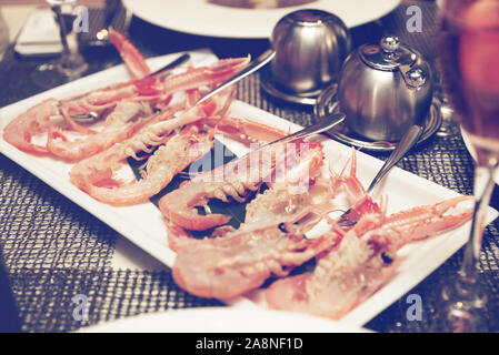 Raw scampi dish on restaurant table - tasty seafood, toned photo - Stock Photo