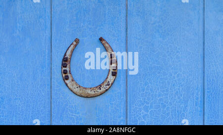 Old iron lucky horseshoe with nails, ends point up to catch the luck, a protective talisman, on a vintage blue wooden door with cracked peeling paint - Stock Photo