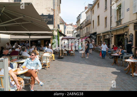 Dijon, Burgundy / France - 27 August 2019: enjoying drinks and food in the patio restaurants in the old city center of Dijon in high summer - Stock Photo