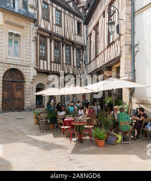 Dijon, Burgundy / France - 27 August 2019: picturesque French outdoor cafe in the historic old town of Dijon with half-timbered houses behind - Stock Photo