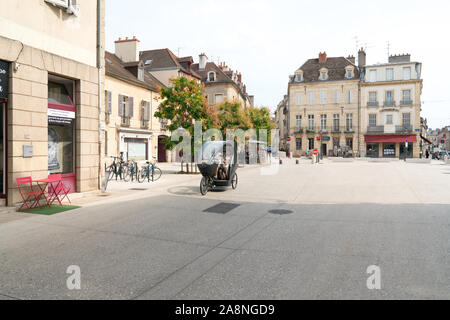 Dijon, Burgundy / France - 27 August 2019: electric bicycle taxi transporting senior citizens through the historic old town of Dijon in Burgundy - Stock Photo
