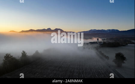 Beautiful foggy autumn morning in Bavaria - aerial view of Wilparting Church before Alps in Chiemgau - Stock Photo