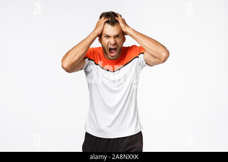 Angry, aggressive mascular sportsman looking furious, grab head in rage and fury, shouting and grimacing from anger and disappointment. Athlete lost