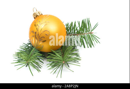 Christmas decoration yellow ball bauble with branches of fir tree on white background - Stock Photo