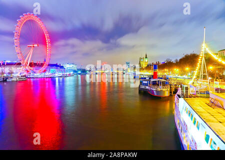 View of the Houses of Parliament and London Eye along the River Thames in London at night.