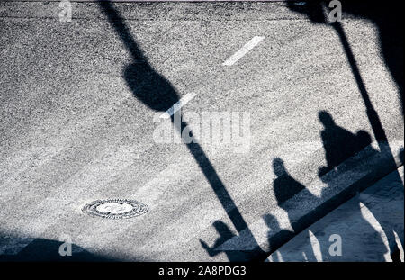 Blurry shadow silhouette of  pedestrians waiting  on city street crossing in the night, from above - Stock Photo