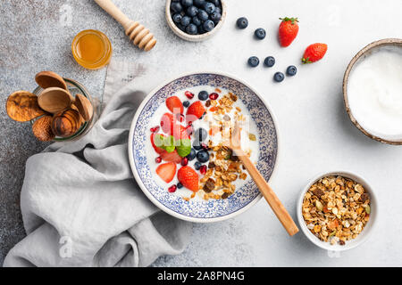 Healthy breakfast yogurt bowl with granola and berries on grey concrete background. Concept of clean eating, dieting and weight loss - Stock Photo