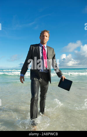 Exhausted young businessman in a full soaking wet suit holding his tablet computer walks from the crashing surf onto a tropical beach - Stock Photo