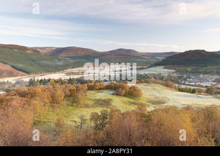 Autumn Colours Dominate the Landscape in this View of the Village of Braemar Nestling in the Mountains on Royal Deeside - Stock Photo