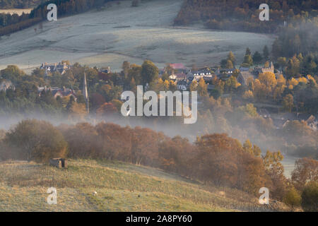 A Misty View of Braemar from the Lower Slopes of Morrone in Autumn, with Braemar & St Margaret's Churches Visible Above the Trees. - Stock Photo