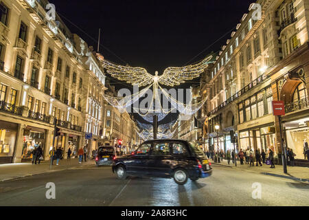 LONDON, UK - 17TH NOVEMBER 2018: Views along Regent Street at night showing Christmas decorations along the street. A typical London Black Cab can be