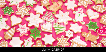 Colorful gingerbread cookies on pink background - Stock Photo
