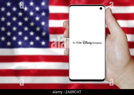 Logo of public company The Walt Disney Company displayed on a smartphone. Flag of USA background. Credit: PIXDUCE - Stock Photo