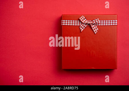 Flat lay a single red Christmas gift on red - Stock Photo