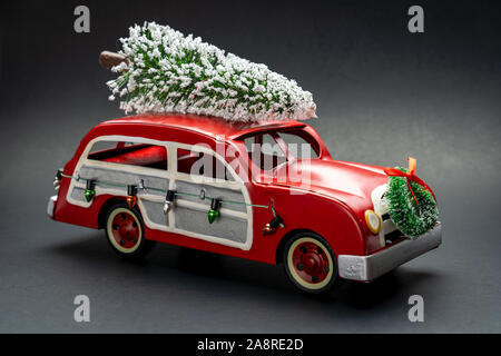 Little red vintage car carrying a Christmas tree on top - Stock Photo