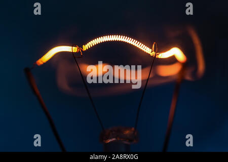 Luminous filament of incandescent lamp close-up on a dark blue background - Stock Photo