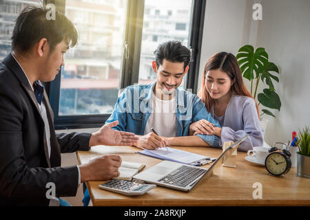 Asian young couple sign contact of house purchase or rental whihc have Sale representative offer the condition in document on the working space table - Stock Photo