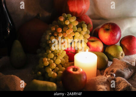 Autumn harvest. White grapes of sultana, apples, pears and pumpkins with soft candle light still life on sackcloth - Stock Photo