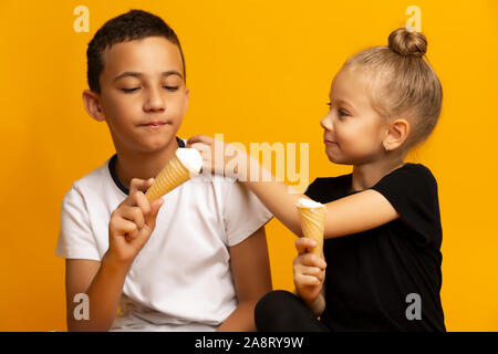 Happy Siblings eating ice-cream on color background - Stock Photo