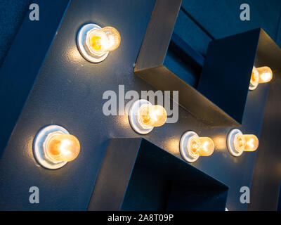 Highlighting outdoor advertising letters with yellow lights - Stock Photo