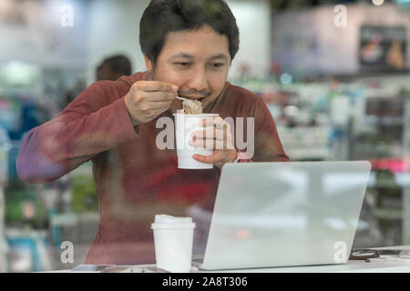 Asian businessman in casual suit eating noodles with urgent action in rush hour at the desk beside the glass in modern office, Business work hard conc - Stock Photo