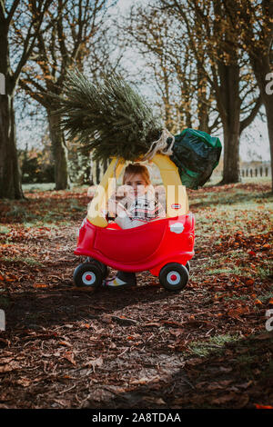 Child driving toy car with christmas tree on top - Stock Photo