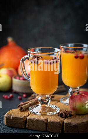Spicy hot pumpkin punch or sangria in a glass with apple, cinnamon, anise. Halloween and Thanksgiving. Traditional autumn, winter drinks and cocktails - Stock Photo