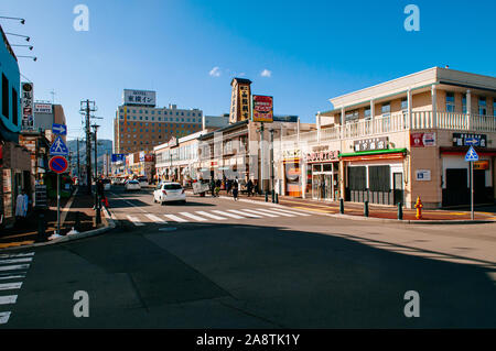 DEC 2, 2018 Hakodate, JAPAN - Asaichi morning fish market and Kaiko street junction under bright sunlight with tourists walking  on sidewalk - Stock Photo
