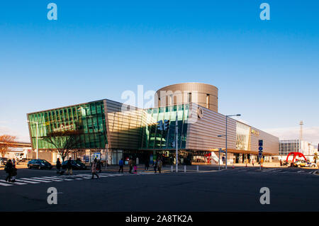 DEC 2, 2018 Hakodate, JAPAN - JR JR Hakodate Station building under bright sunlight in winter with tourists crossing road at junction. - Stock Photo