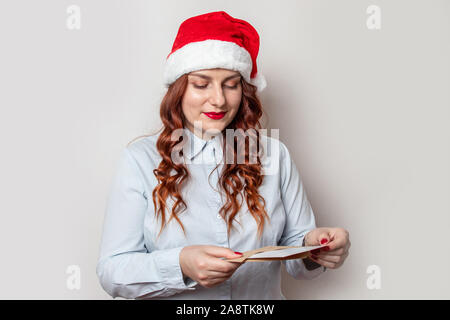 Young red-haired girl in a red santa hat reads a letter, standing against a gray wall in the office. Preparing for Christmas and New Year - Stock Photo