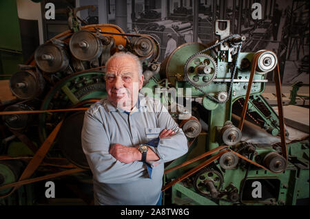 83 year Roland Schulze who worked on the production of the East German Trabant in the time of the DDR stands beside some of the machinery used. - Stock Photo