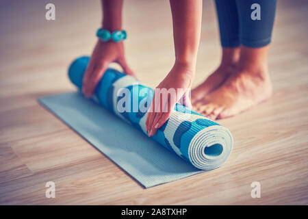 Young woman rolling yoga mat at home - Stock Photo
