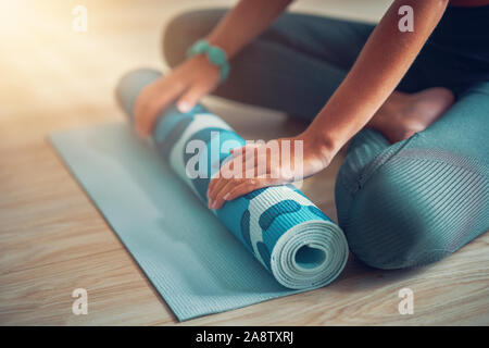 Young woman rolling yoga mat at home